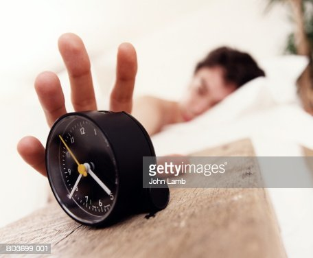 Young man in bed reaching for alarm clock : Stock Photo
