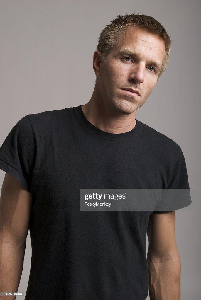 Young Man in Black T-Shirt Looks at Camera Bad Attitude