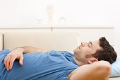"""Young man in blue t-shirt sleeping on couch in living room. Click here for more """"People at Home"""" images:"""