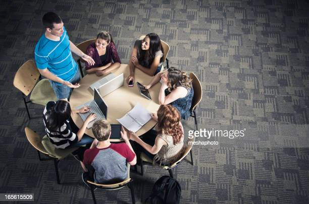 Young man in blue shirt talking to study group