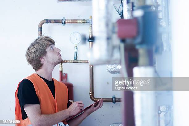 Young man in boiler room holding clipboard inspecting heating system, looking up