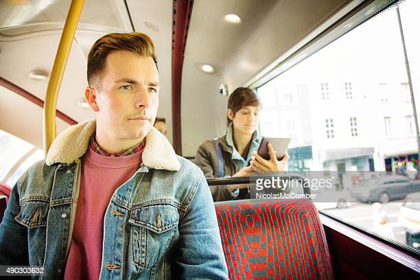 Young man in bus through London rainy day