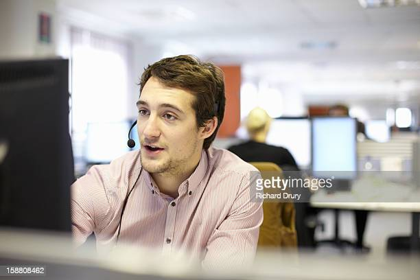Young man in call centre office