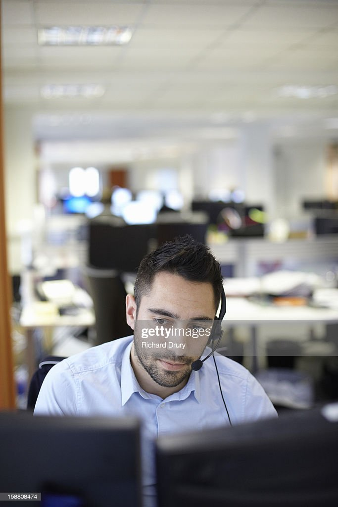 Young man in call centre office : Stock Photo