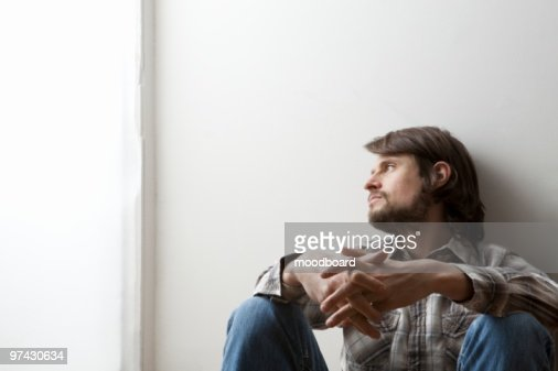 Young man in checked shirt sits with hands clasped against a wall : Stock Photo
