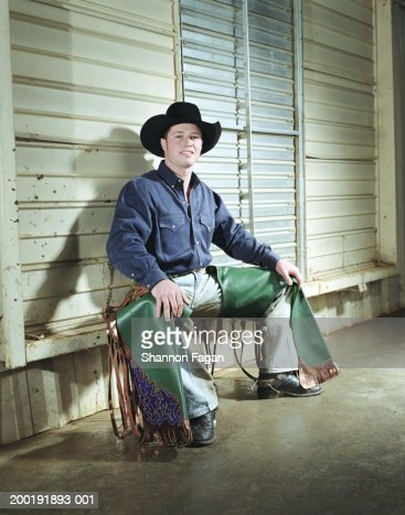 Young man in cowboy hat and chaps smiling, portrait : Stock Photo