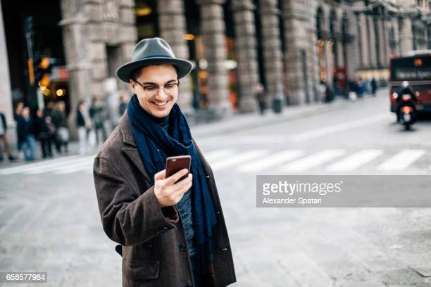Young man in eyeglasses and hat looking at his mobile phone on the street of Bologna, Italy