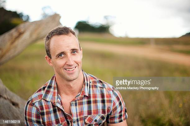 Young man in field smiling