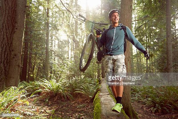 Young man in forest, carrying mountain bike over fallen tree