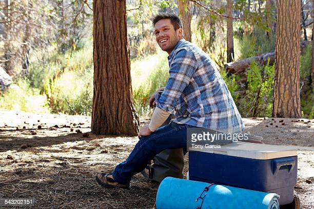 Young man in forest sitting on cool box, Los Angeles, California, USA