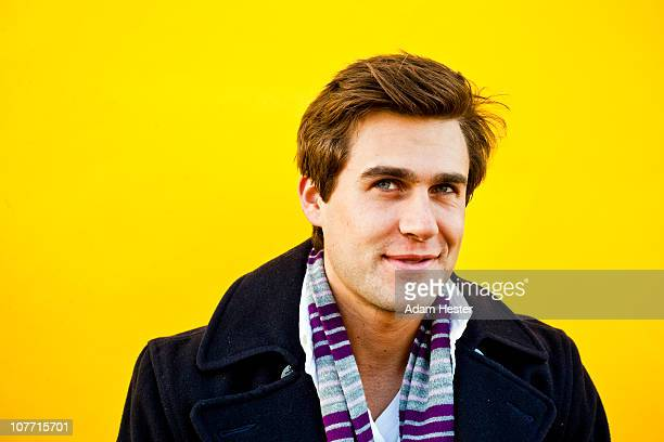 A young man in front of a yellow backdrop.