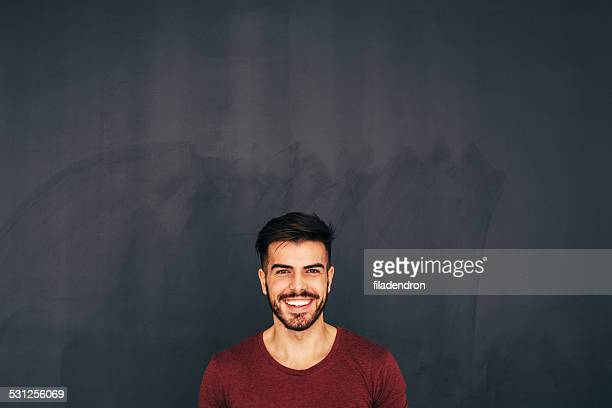 Young man in front of blackboard