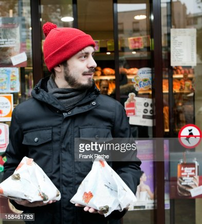 young man in front of store holding two packages : Stock Photo