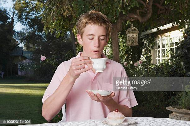 Young man in garden, drinking tea from china cup