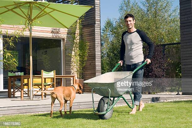 Young man in garden, pushing wheel barrow