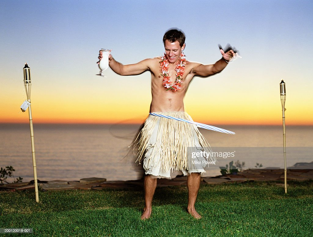 Young man in grass skirt playing with plastic hoop : Stock Photo