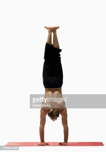 Young man in handstand yoga pose, rear view : Stock Photo