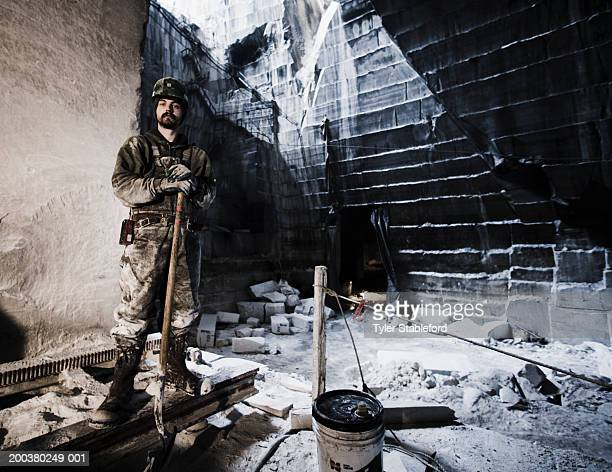 Young man in hardhat standing in marble quarry, portrait