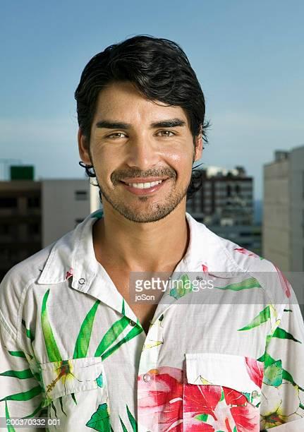 Young man in hawaiian shirt smiling, portrait, close-up