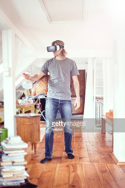 Young man in his apartment, using VR glasses
