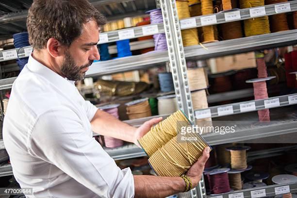 Giovane uomo con la manifattura artigianale tradizionale Stabilimento tessile