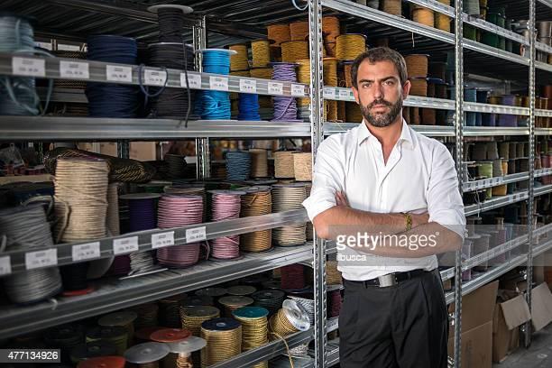 Junger Mann in seinem meisterhafte Handwerkskunst traditionellen Textilfabrik