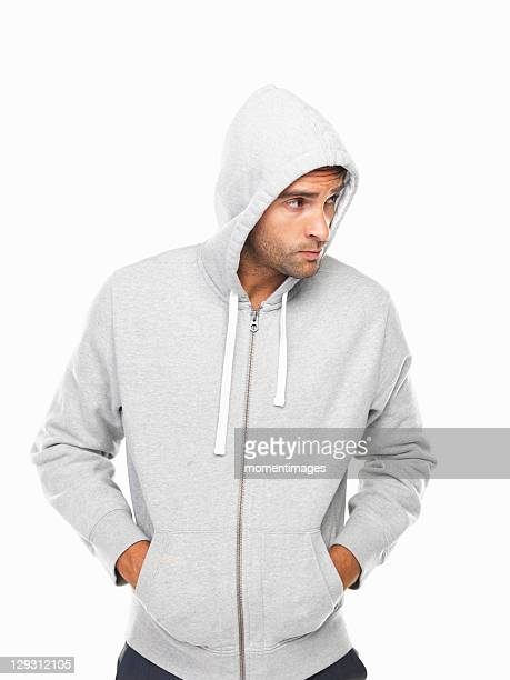 Young man in hoodie standing with hands in pockets