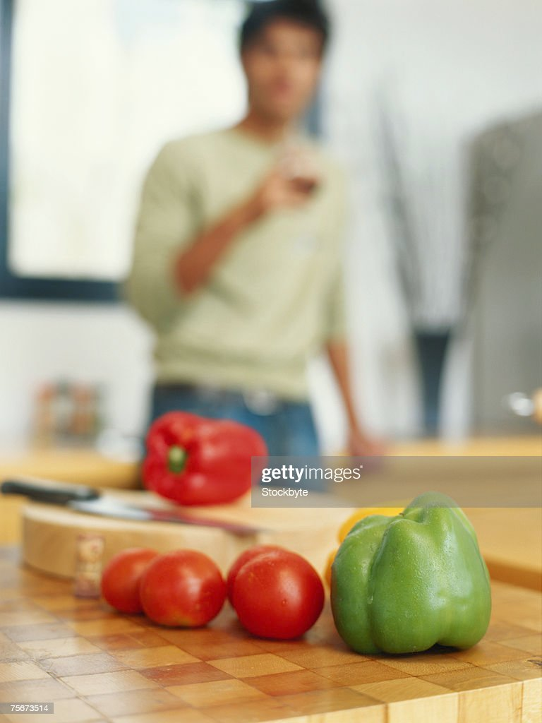 Young man in kitchen with focus on vegetables in foreground : Stock Photo