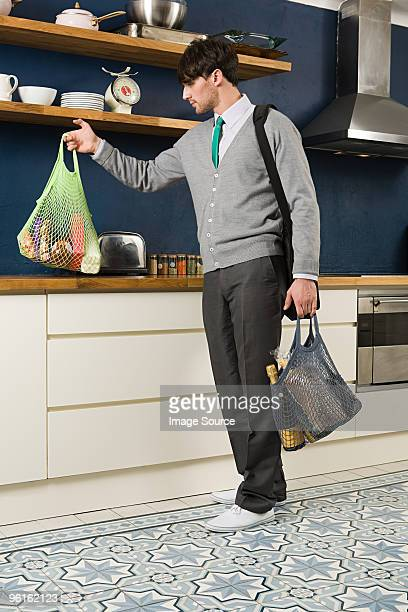 Young man in kitchen with groceries
