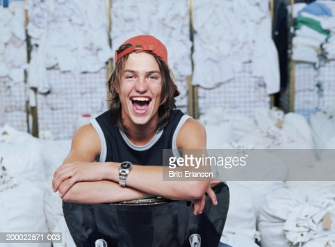 Young man in laundry, laughing, portrait