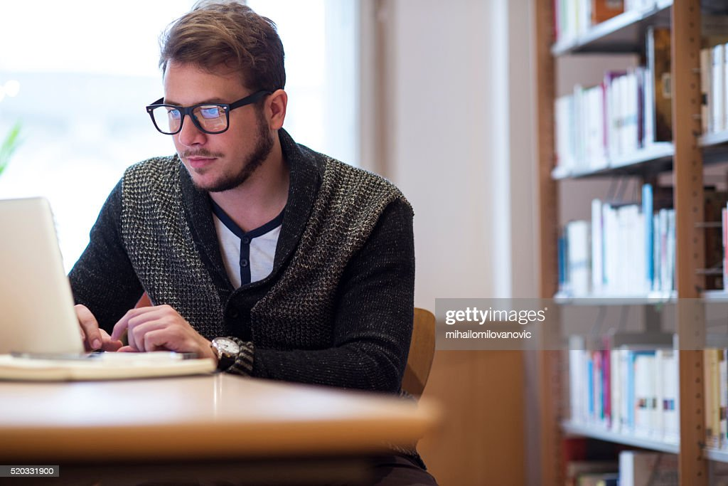 Young man in library : Stock Photo