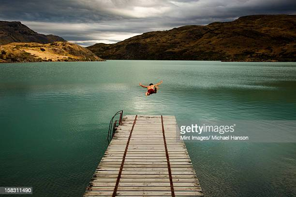 A young man in mid air, diving off a wooden pier, into calm lake surrounded by mountains in Torres del Paine National Park, Chile.