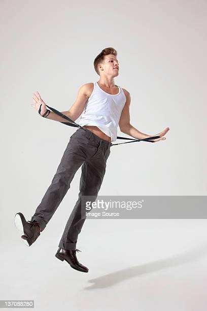 Junger Mann in der Luft ziehen Hose Hosenträger