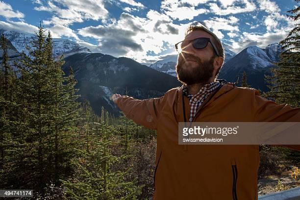Jeune homme détente dans la nature, les bras tendus