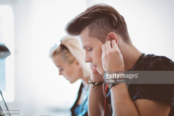 Young man in office adjusting earphones