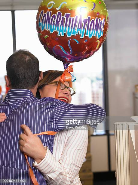 Young man in office embracing female colleague holding 'congratulations' balloon