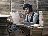 Young man in old fashioned costume making research among newspapers