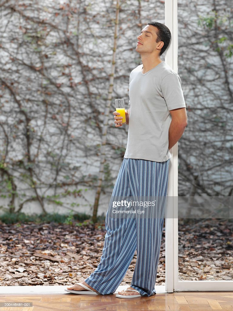 Young man in pajamas leaning against window post, holding juice : Stock Photo