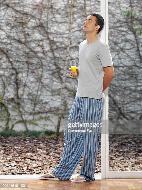 Young man in pajamas leaning against window post, holding juice