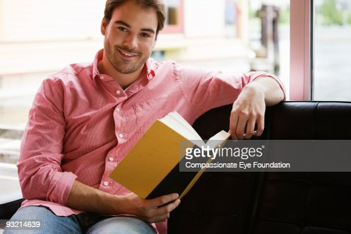 Young Man In Pink Shirt Holding A Book Stock Photo | Getty Images