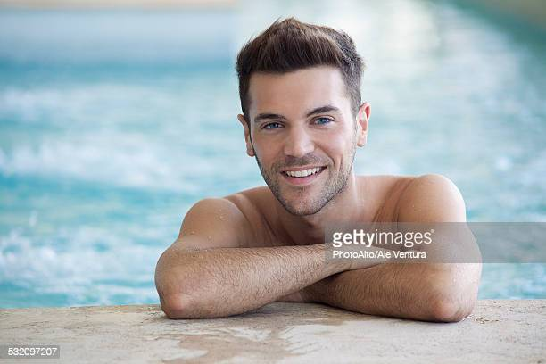 Young man in pool resting against wall