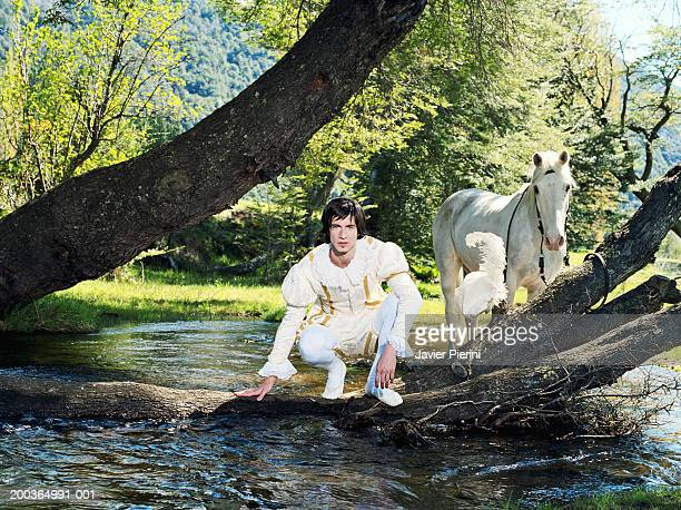 Young man in prince costume crouching by river, horse in background
