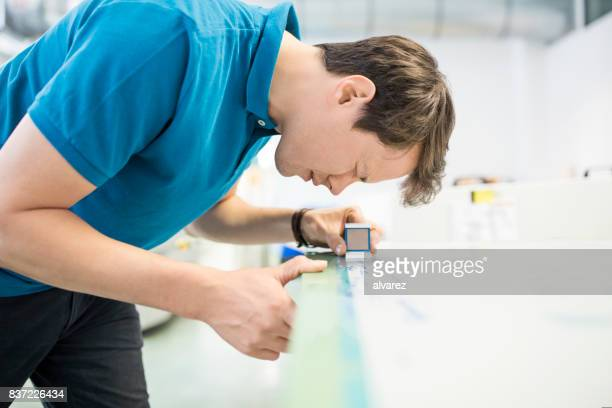 Young man in printing press using magnifying glass