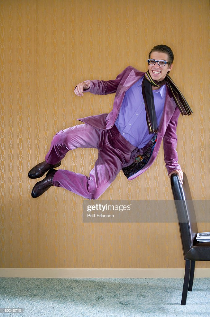 Young man in purple suit jumps for joy. : Stock Photo