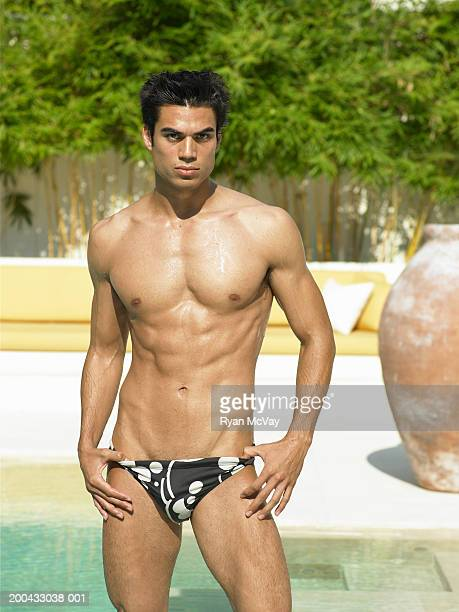 Young man in racing briefs standing beside pool, hands on hips