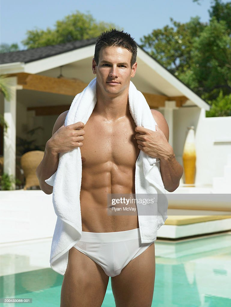 Young man in racing briefs standing beside pool, towel around neck