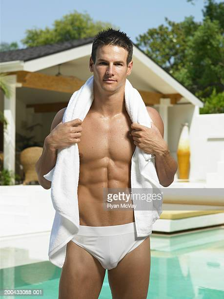Young man in racing briefs standing beside pool, towel around neck
