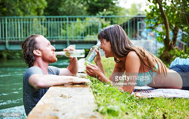 Young man in river, young woman lying on grass at edge of river, man drinking from beer bottle