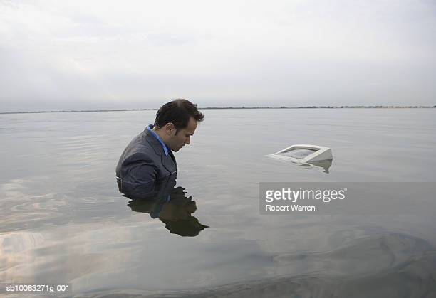 Young man in shallow water with computer monitor floating besides