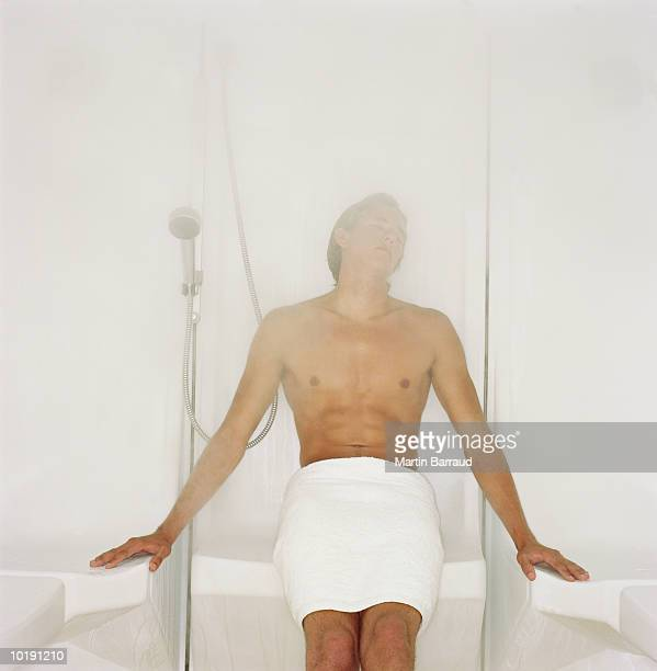 Young man in shower room, relaxing